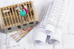 Casa sob a construção, as chaves, as moedas euro- e os desenhos bondes, conceito da casa da construção Imagens de Stock Royalty Free