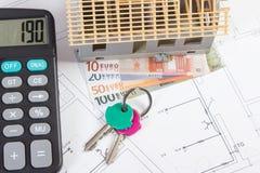 Casa sob a construção, as chaves, a calculadora e as moedas euro- em desenhos bondes, conceito da casa da construção Fotografia de Stock Royalty Free