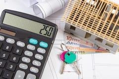 Casa sob a construção, as chaves, a calculadora e as moedas euro- em desenhos e em diagramas bondes Imagens de Stock Royalty Free