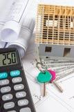 Casa sob a construção, as chaves, a calculadora, o dólar das moedas e os desenhos bondes, conceito da casa da construção Imagem de Stock Royalty Free