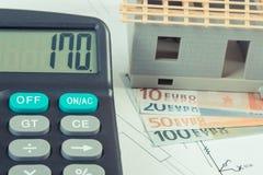 Casa sob a construção, a calculadora e as moedas euro- em desenhos e em diagramas bondes Imagem de Stock