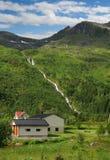 Casa sob a montanha com quedas. Fotos de Stock