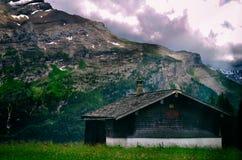 Casa sola nel legno con il backgr del cielo nuvoloso e della grande montagna Fotografia Stock Libera da Diritti