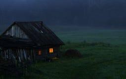 Casa sola torva alla notte in un campo Fotografia Stock Libera da Diritti