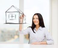 Casa sorridente del disegno della donna sullo schermo virtuale Fotografia Stock