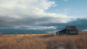 Casa sozinha pequena contra o campo do céu nebuloso na primavera, tempo-lapso vídeos de arquivo