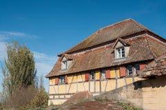 Casa storica in villaggio alsaziano sul fondo del cielo blu Immagine Stock
