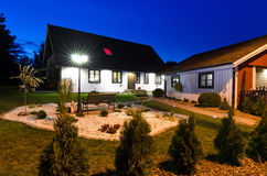 Casa sueca del chalet con el jardín moderno en la noche Imagen de archivo libre de regalías