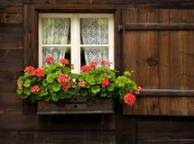 Casa suiza con Flowerbox en ventana Fotografía de archivo libre de regalías