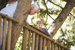 Casa sull'albero della costruzione del nipote e del nonno insieme Immagine Stock