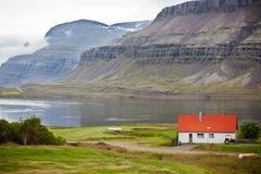 Casa típica de la granja en la costa islandesa del fiordo Foto de archivo