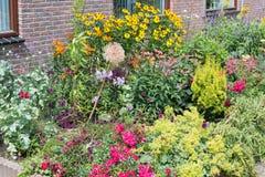 A casa tem o jardim da frente com diversas plantas de florescência Fotos de Stock