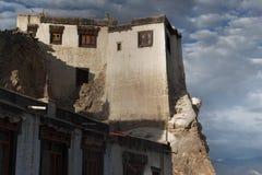 Casa tibetana tradizionale sulla roccia: alta parete bianca, alla cima della finestra con la struttura di legno, terrazzo, contro Fotografia Stock