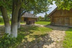 Casa tradizionale del villaggio con cielo blu, erba verde, il recinto e gli alberi l'ucraina Casa tradizionale del villaggio con  Fotografie Stock Libere da Diritti