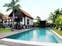 Casa tropical del estilo con la piscina y ajardinar Fotos de archivo libres de regalías