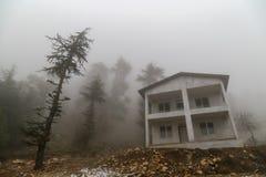 Casa vacía en bosque nublado en una montaña Árboles de pino en niebla cerca del edificio concreto inacabado imagen de archivo libre de regalías
