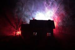 Casa velha com Ghost na floresta na noite ou casa assombrada abandonada do horror na névoa Construção místico velha na floresta i Fotos de Stock Royalty Free