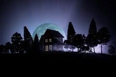 Casa velha com Ghost na floresta na noite ou casa assombrada abandonada do horror na névoa Construção místico velha na floresta i Fotografia de Stock Royalty Free