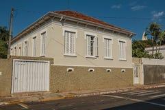 Casa velha da classe obreira com porta da garagem e palmeira em uma rua vazia em um dia ensolarado em San Manuel foto de stock