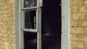 A casa velha do tijolo com vidro quebrado das janelas na floresta, câmera move-se para dentro e mostra-se a sala escura filme