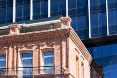 A casa velha pequena do tijolo e a construção moderna do vidro e do aço estão proximamente entre si Fotos de Stock Royalty Free