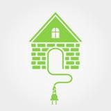 Casa verde con el zócalo, icono casero de la electricidad Fotos de archivo