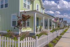 Casa verde in vicinanza con il recinto bianco Fotografia Stock