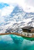 Casa vicino ad un lago della montagna in alpi svizzere Fotografia Stock Libera da Diritti