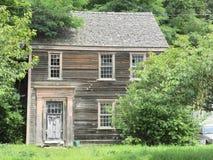 Casa vieja abandonada con la peladura de la pintura y yarda y árboles demasiado grandes para su edad foto de archivo libre de regalías