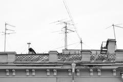Casa vieja con las chimeneas y las antenas de televisión imágenes de archivo libres de regalías