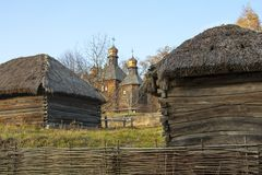 Casa vieja de los campesinos con un tejado y una iglesia de la paja en el Museo Nacional ucraniano Pirogovo Kyiv, Ucrania imágenes de archivo libres de regalías