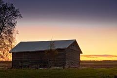 Casa vieja del granero en la puesta del sol de la primavera Foto de archivo libre de regalías
