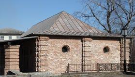 Casa vieja del ladrillo con las pequeñas ventanas redondas Fotografía de archivo libre de regalías