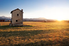 Casa vieja en campo en la puesta del sol Fotografía de archivo libre de regalías