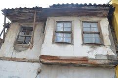 Casa vieja hecha de la madera y de la piedra con las ventanas quebradas Imágenes de archivo libres de regalías