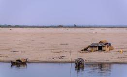 Casa y barcos en riverbanks Foto de archivo libre de regalías