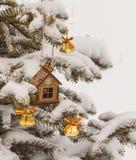 Casa y campanas del juguete de la Navidad en picea Imágenes de archivo libres de regalías