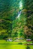 Casa y cascada del pueblo de Noruega imagenes de archivo