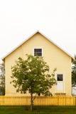 Casa y cerca amarillas con el árbol rojo y verde Fotografía de archivo libre de regalías
