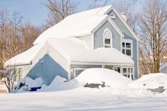 Casa y coches después de la tempestad de nieve Imágenes de archivo libres de regalías