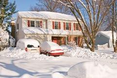 Casa y coches después de la tempestad de nieve Foto de archivo libre de regalías