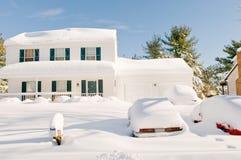 Casa y coches después de la tempestad de nieve Fotografía de archivo