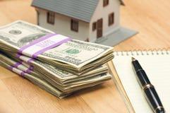 Casa y dinero con la pista y la pluma Fotos de archivo libres de regalías