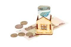 Casa y dinero en un fondo blanco Imagen de archivo