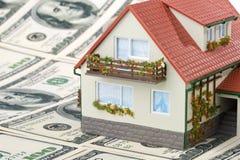 Casa y dinero miniatura. Foto de archivo