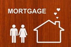 Casa y familia de papel con el texto de la hipoteca Imagen conceptual Fotografía de archivo libre de regalías