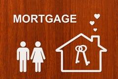 Casa y familia de papel con el texto de la hipoteca Imagen conceptual Imagen de archivo libre de regalías