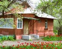Casa y jardín con los tulipanes Fotos de archivo