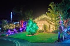 Casa y jardín encendidos brillantemente con las luces de la Navidad multicoloras fotografía de archivo