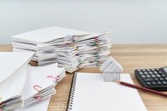 Casa y lápiz en el cuaderno con el fondo del blanco de la calculadora Imagen de archivo